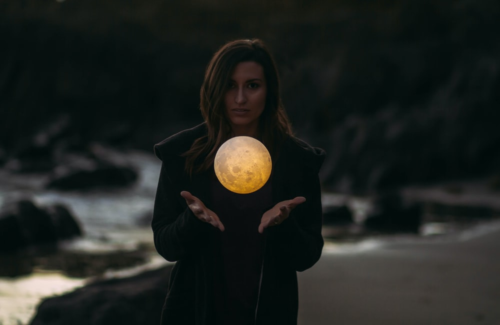 woman wearing black jacket standing near water