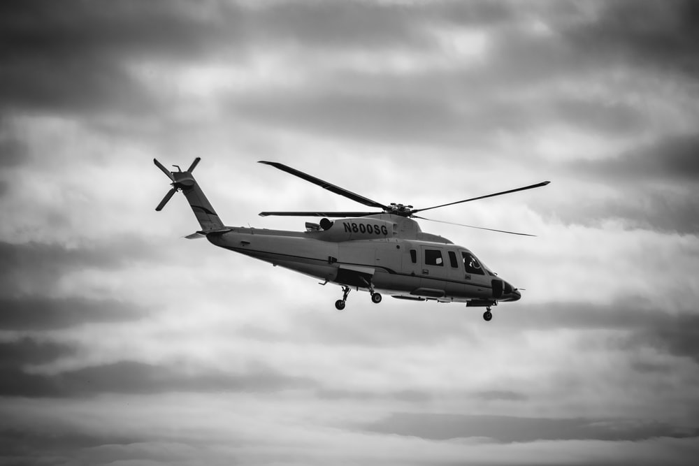 gray helicopter on flight grayscale photo