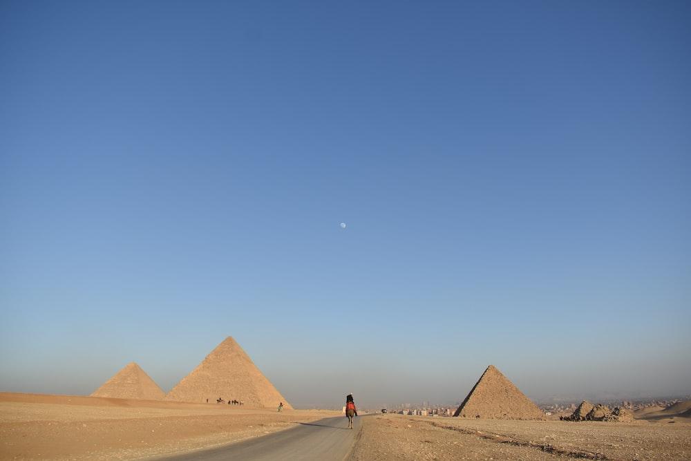 person walking near pyramids during daytime