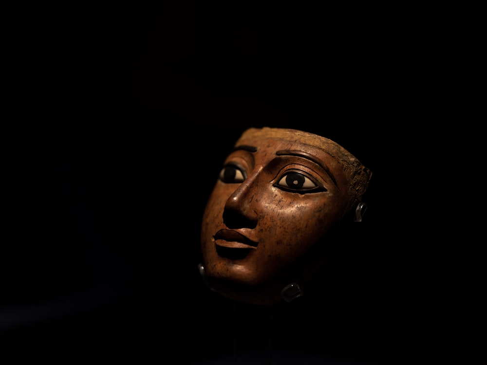 brown wooden mask inside dark room