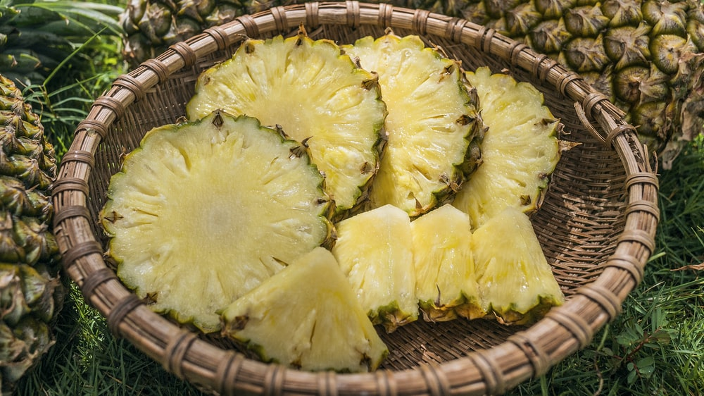 sliced pineapples served on brown basket
