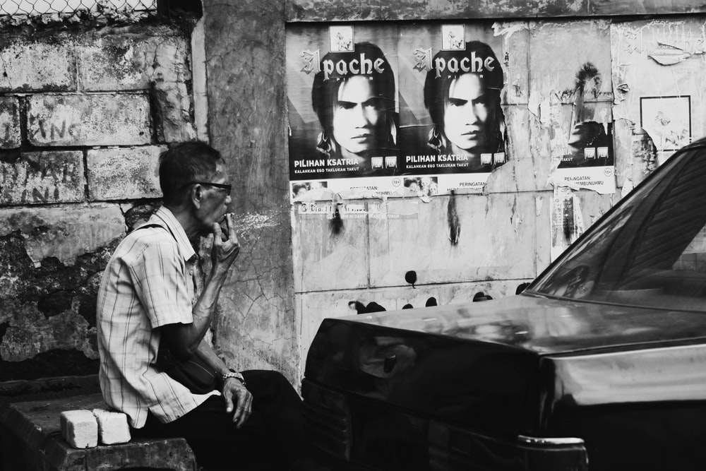 grayscale photography of man smoking near vehicle