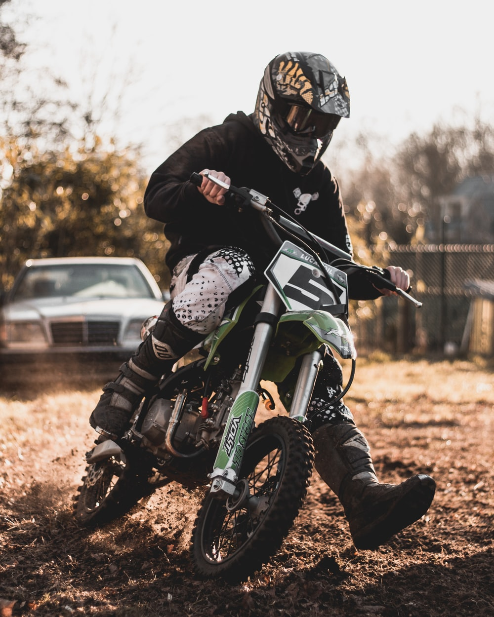 man riding on black and green motocross dirt bike