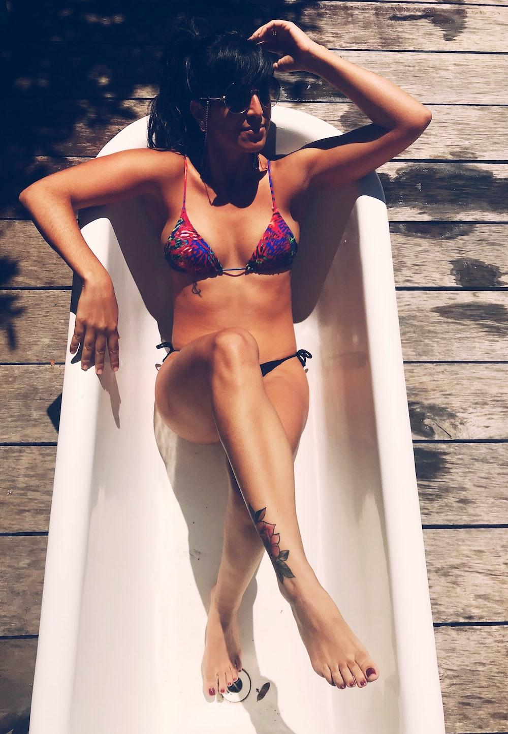 woman wearing purple bikini sitting on white ceramic bath tub