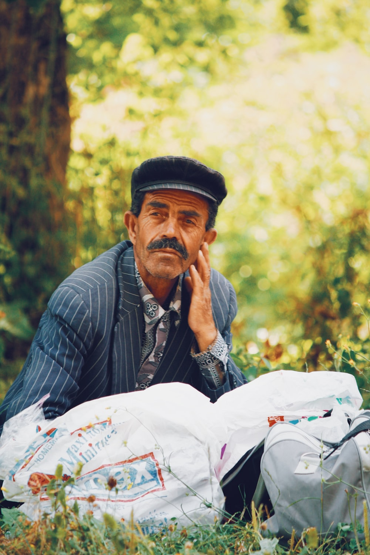 man wearing cap sitting on green grass field outdoor