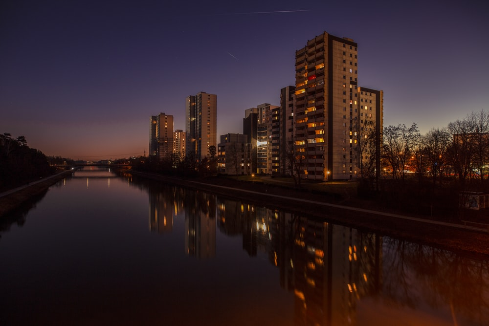 brown concrete building beside water