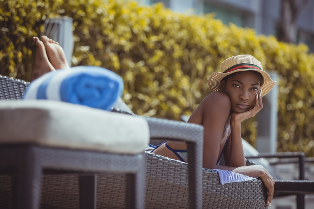 woman lying on brown wicker bench