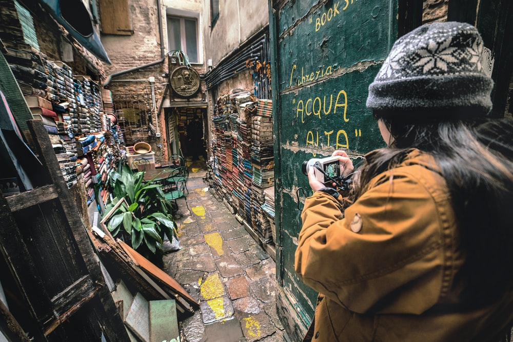 woman taking photo of an alley