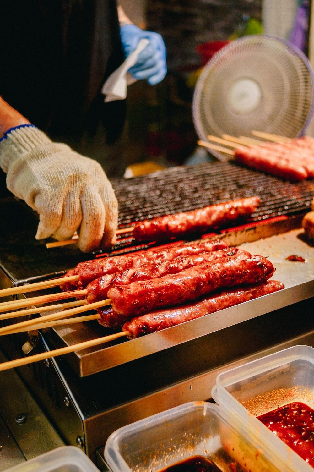 person grilling hotdogs