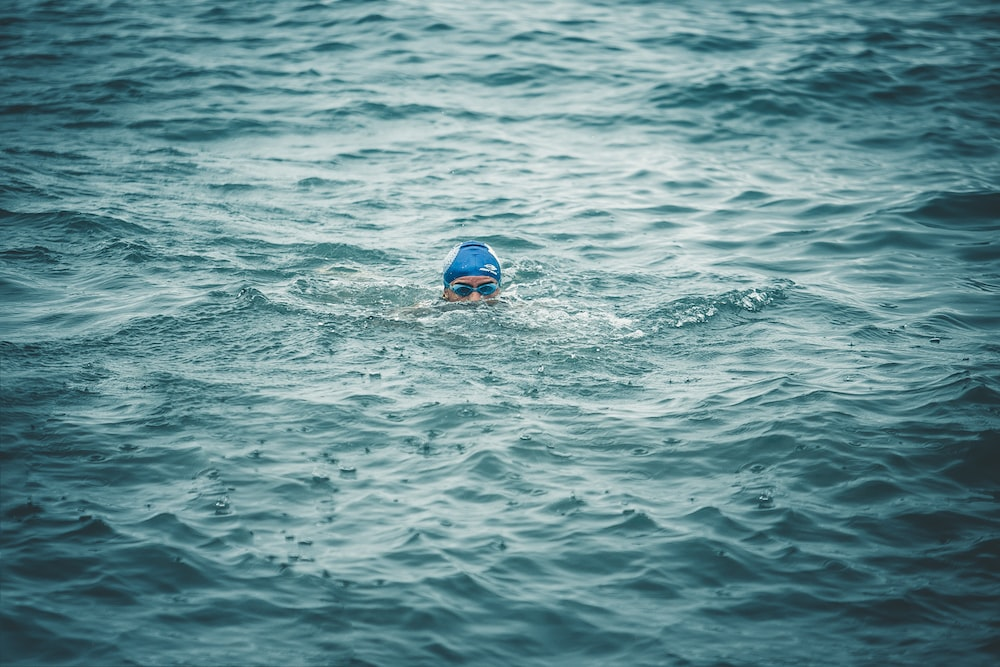 person swimming on body of water during daytime