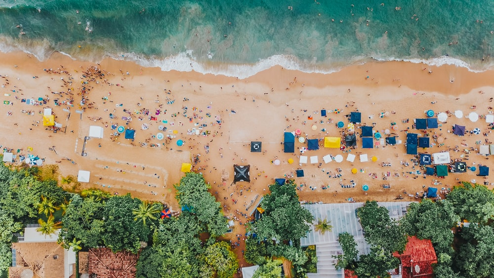 aerial view of beach filled with people and stalls