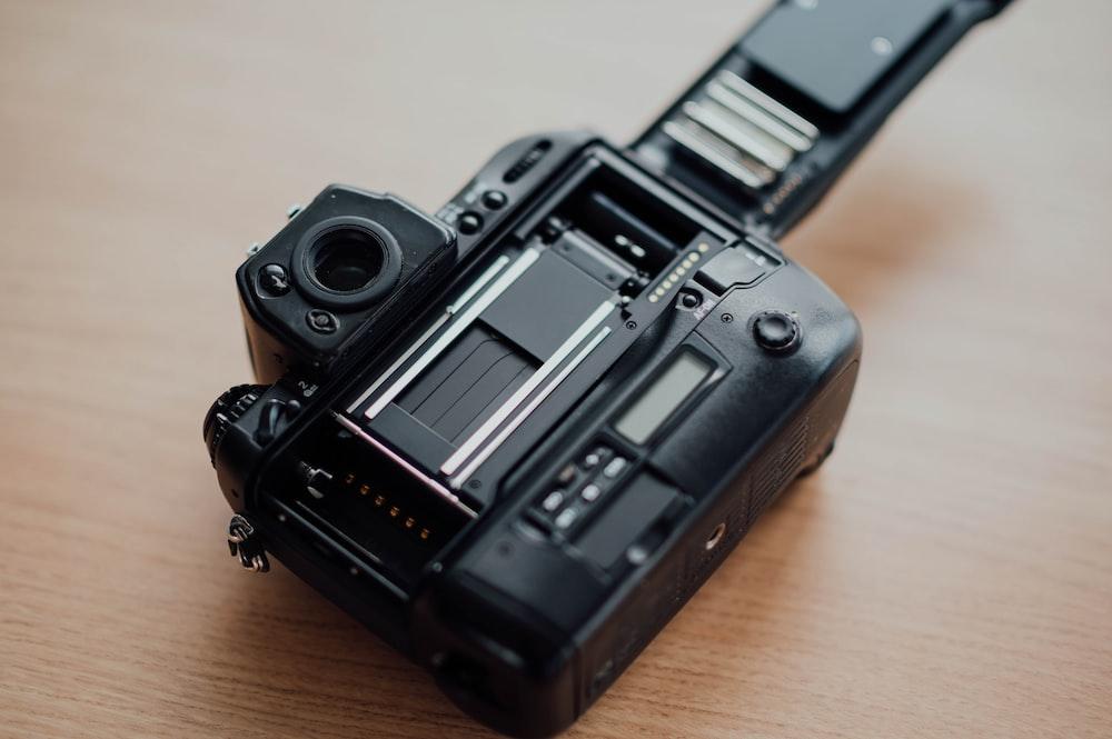 black SLR camera on brown surface