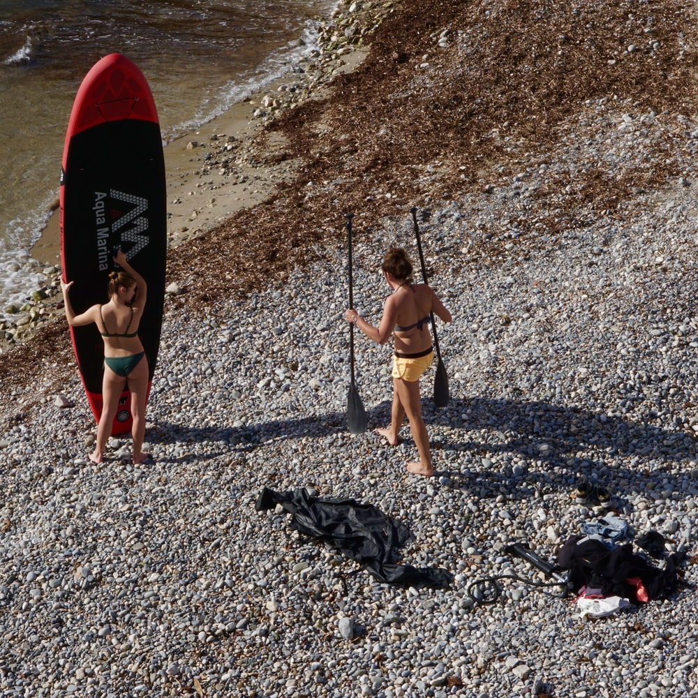 woman holding paddle board near woman holding paddles