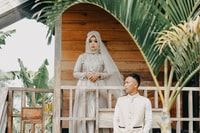 newly wed couple sitting and standing on terrace
