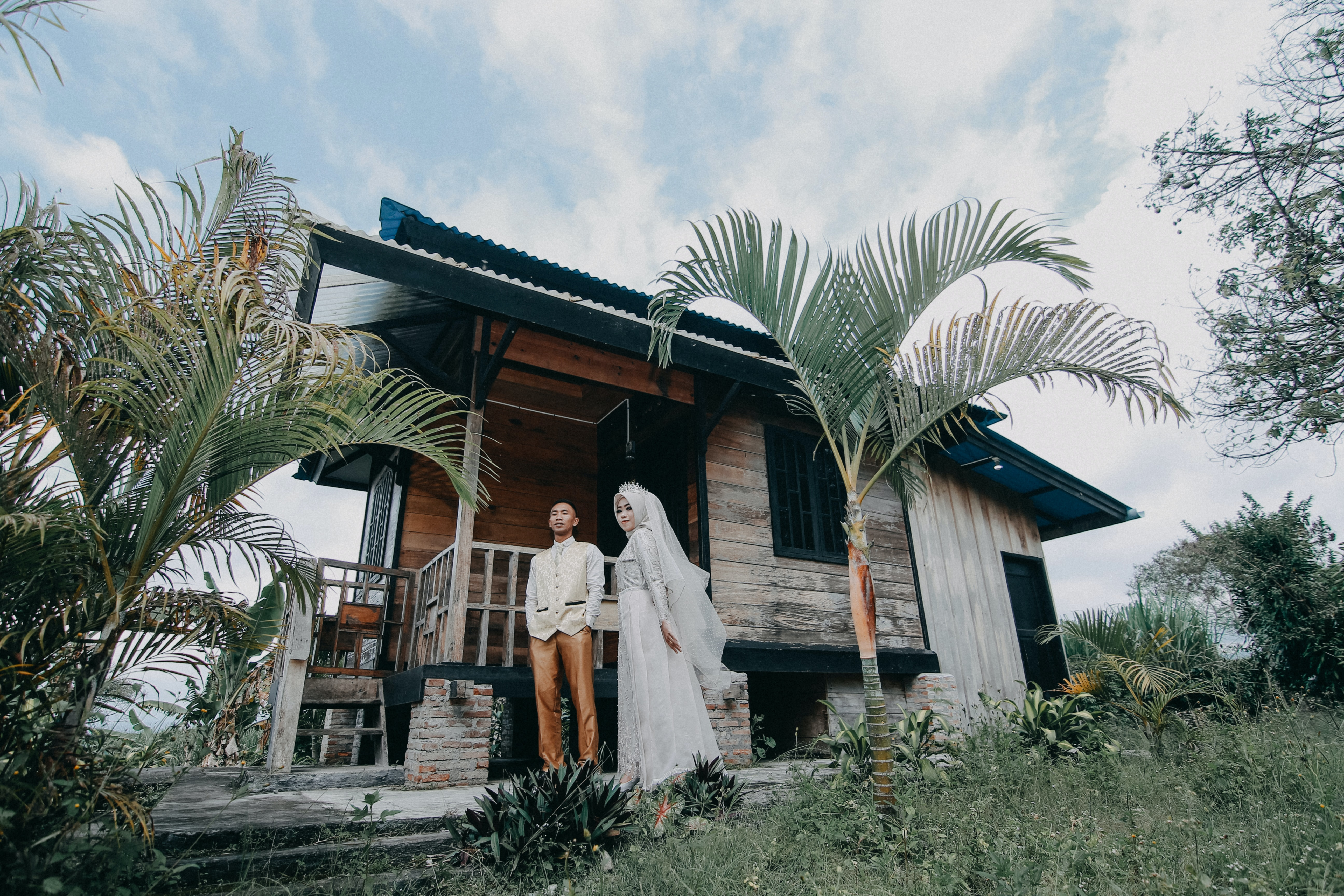 newly wed couple standing outside the wooden bungalow during day time