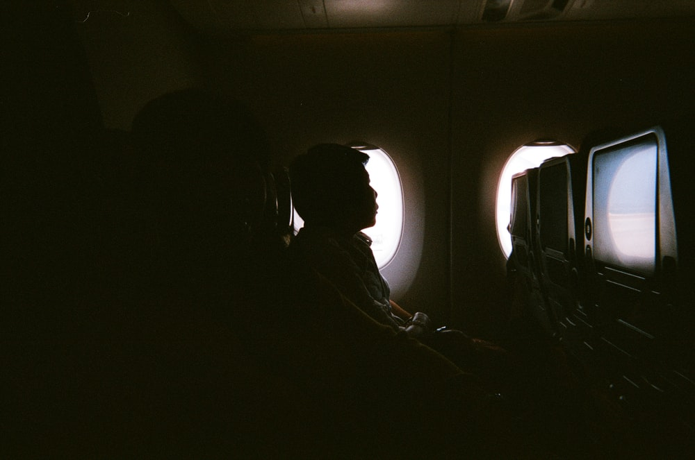 man sitting beside air plane mirror