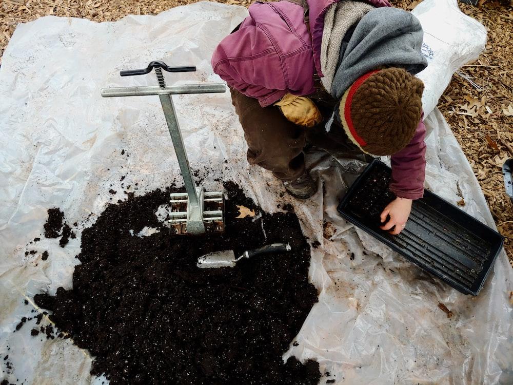 man kneeling beside black soil