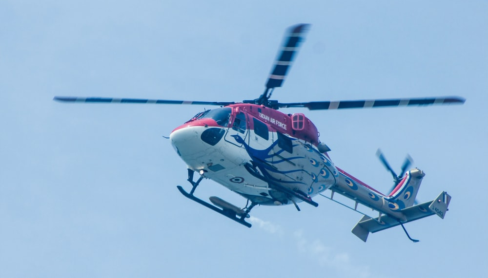 white, red, and gray helicopter flying
