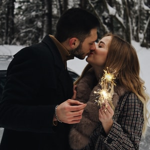 man and woman kissing while holding fireworks