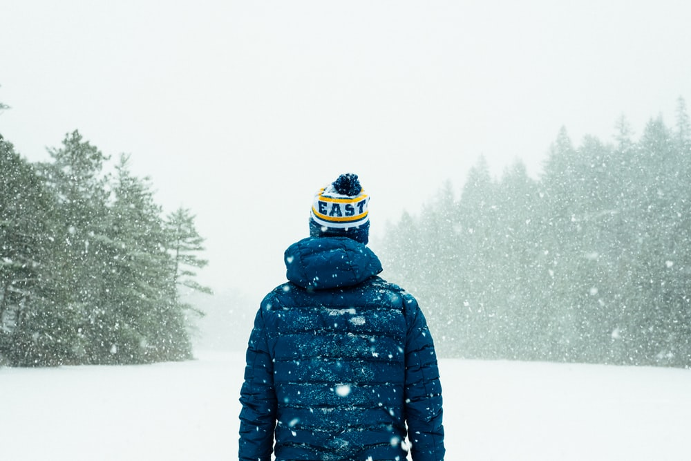 person in blue jacket standing on snow-covered ground