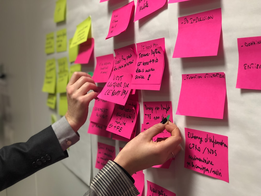 person holding pink sticky notes