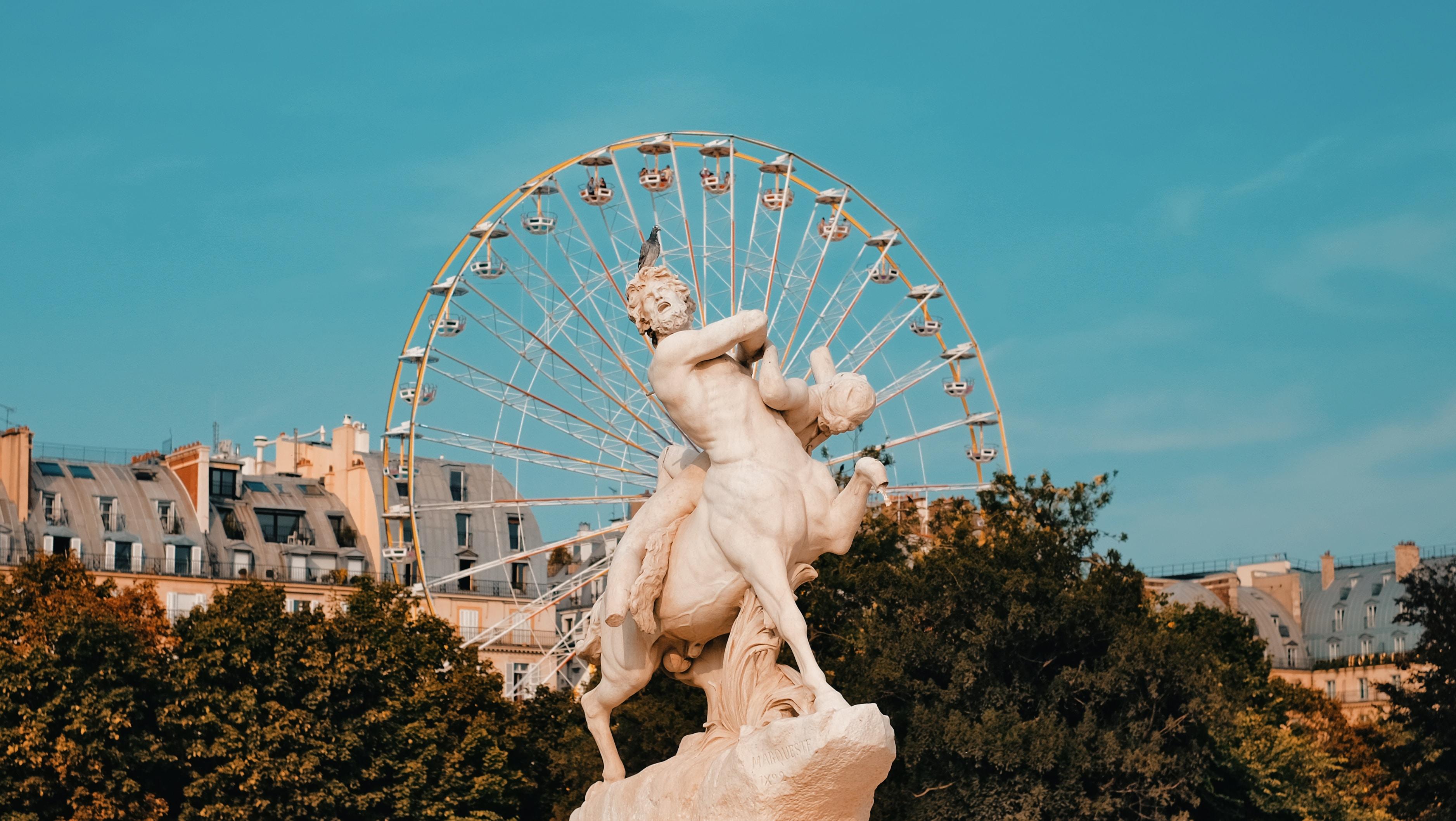 Centaur statue near trees with view of Ferris wheel during daytim