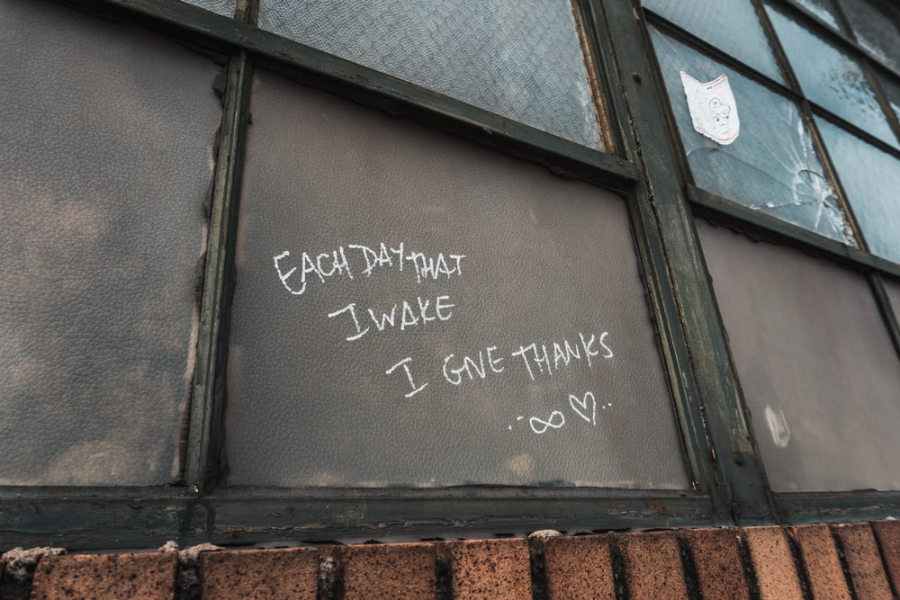 each day that I wake I give thanks written on window