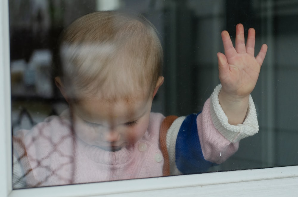 child behind clear glass