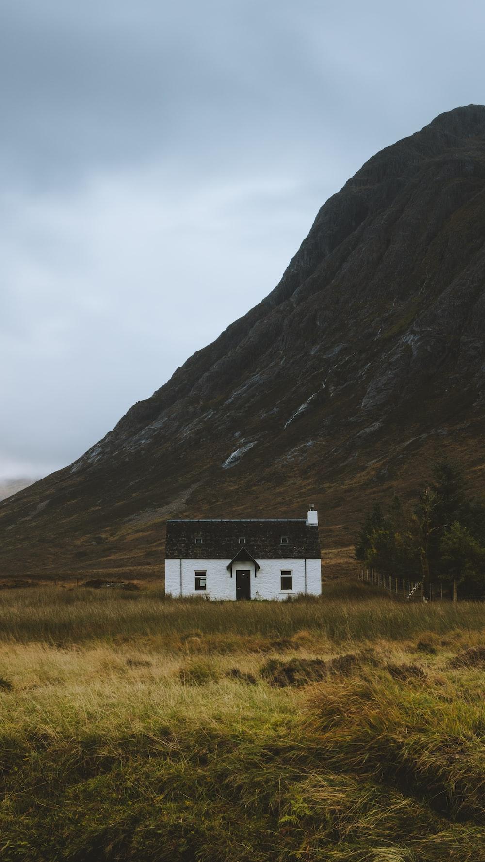 white concrete house by mountain