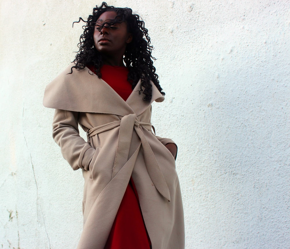 woman wearing brown coat with hands in her pockets