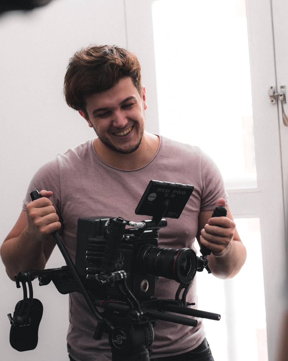 man standing beside DSLR camera