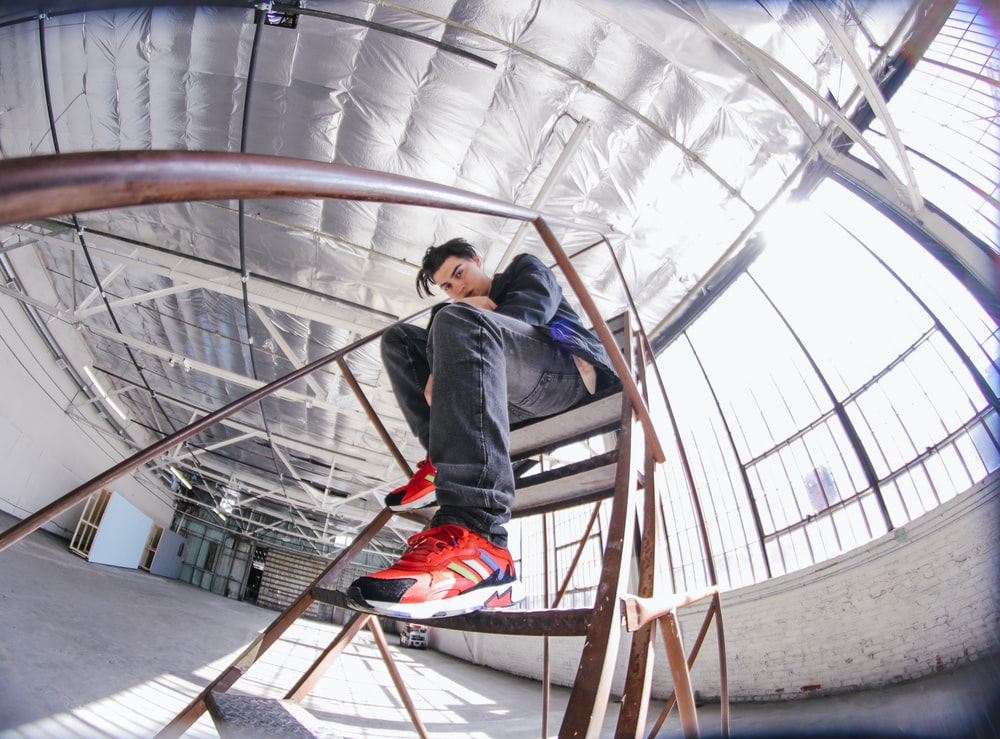 man sitting on brown metal portable stairs