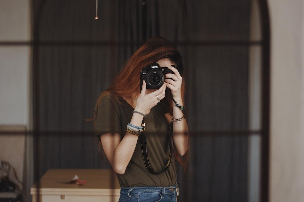 woman taking photo using DSLR camera