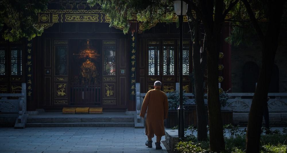 man walking through brown wooden building during daytime