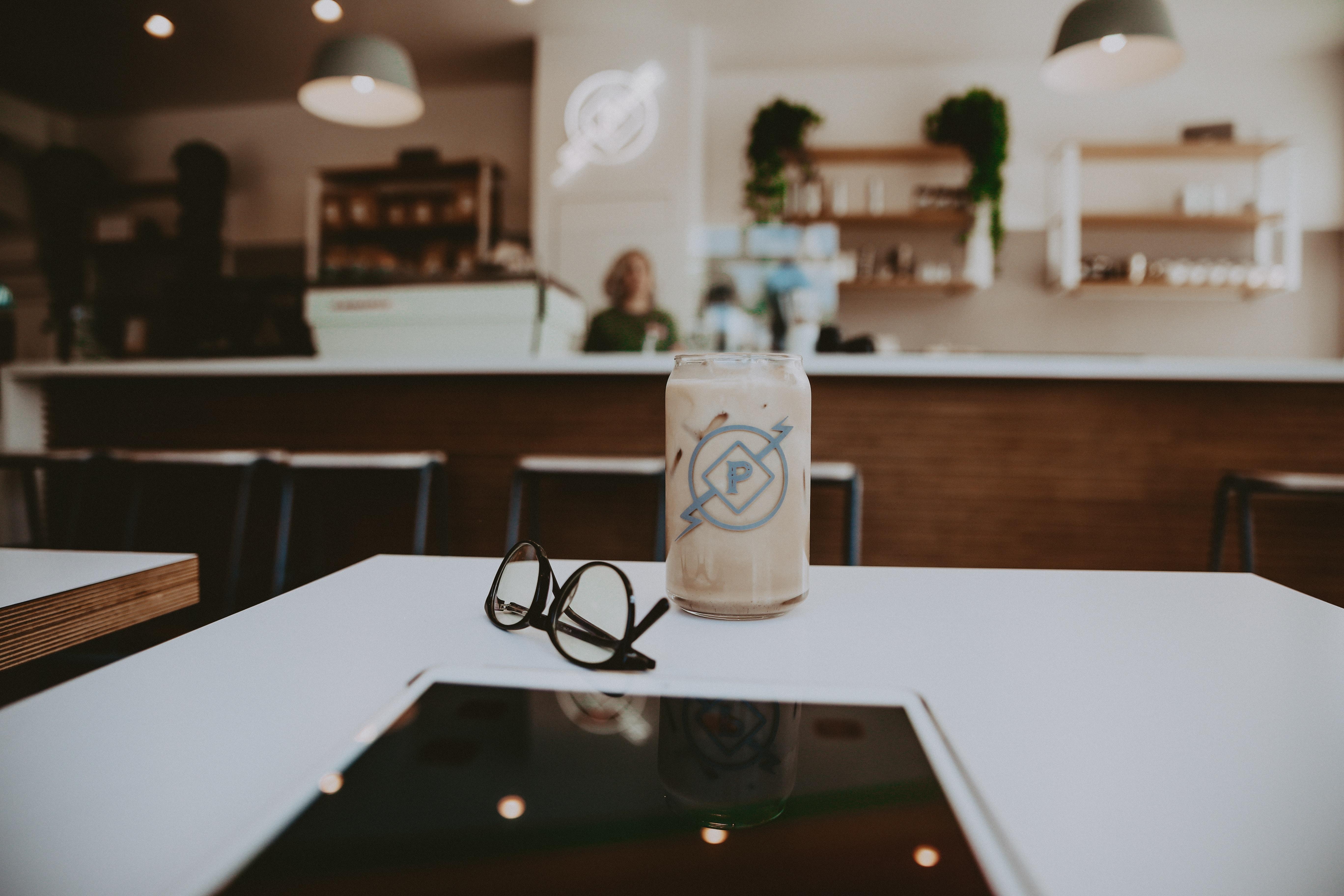 black framed eyeglasses beside glass cup on white wooden table