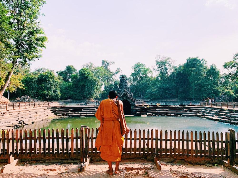 monk standing across body of water
