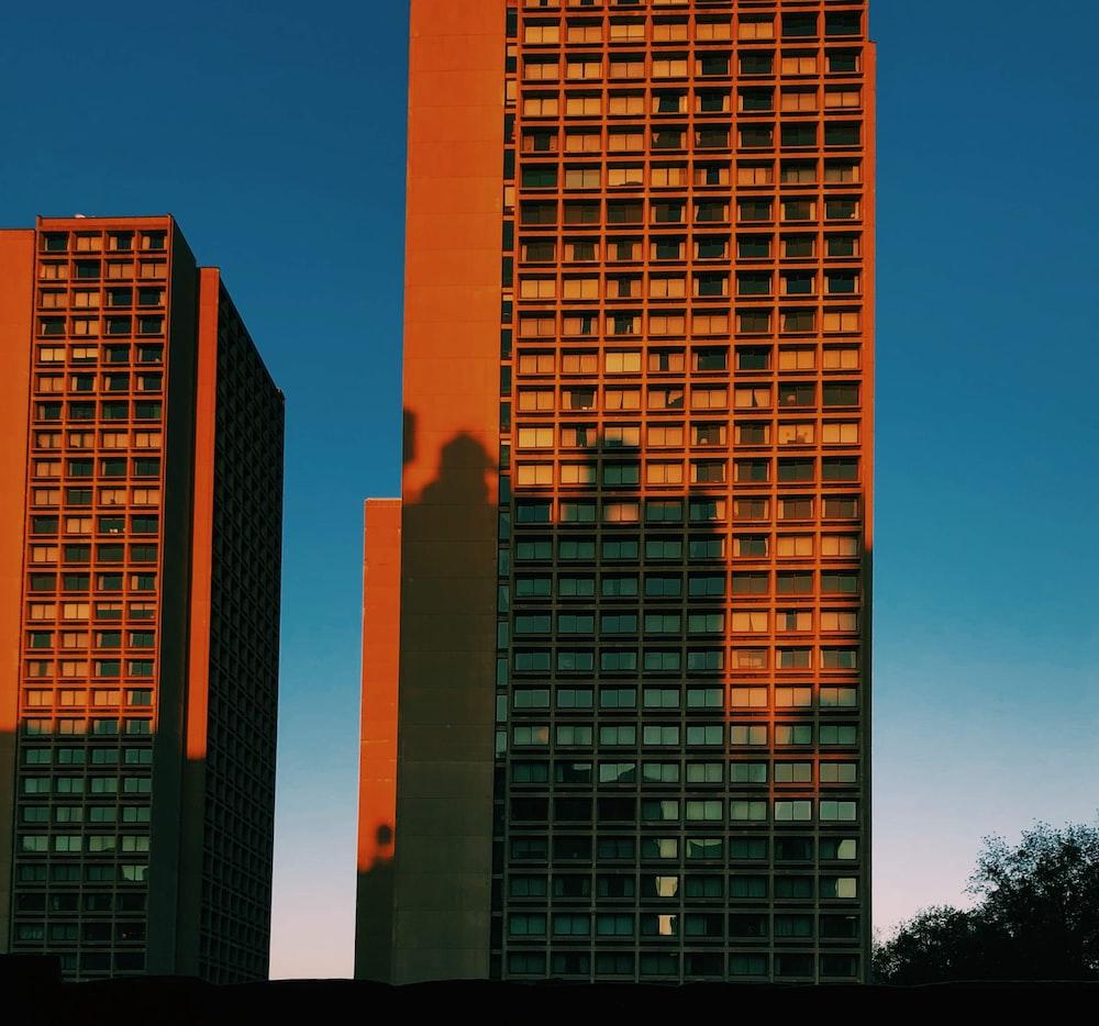 two brown concrete buildings under clear blue sky