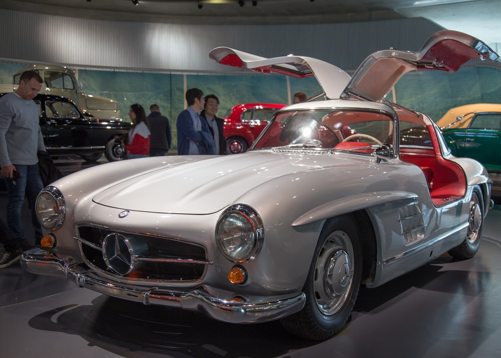 people in front of classic silver Mercedes-Benz vehicle