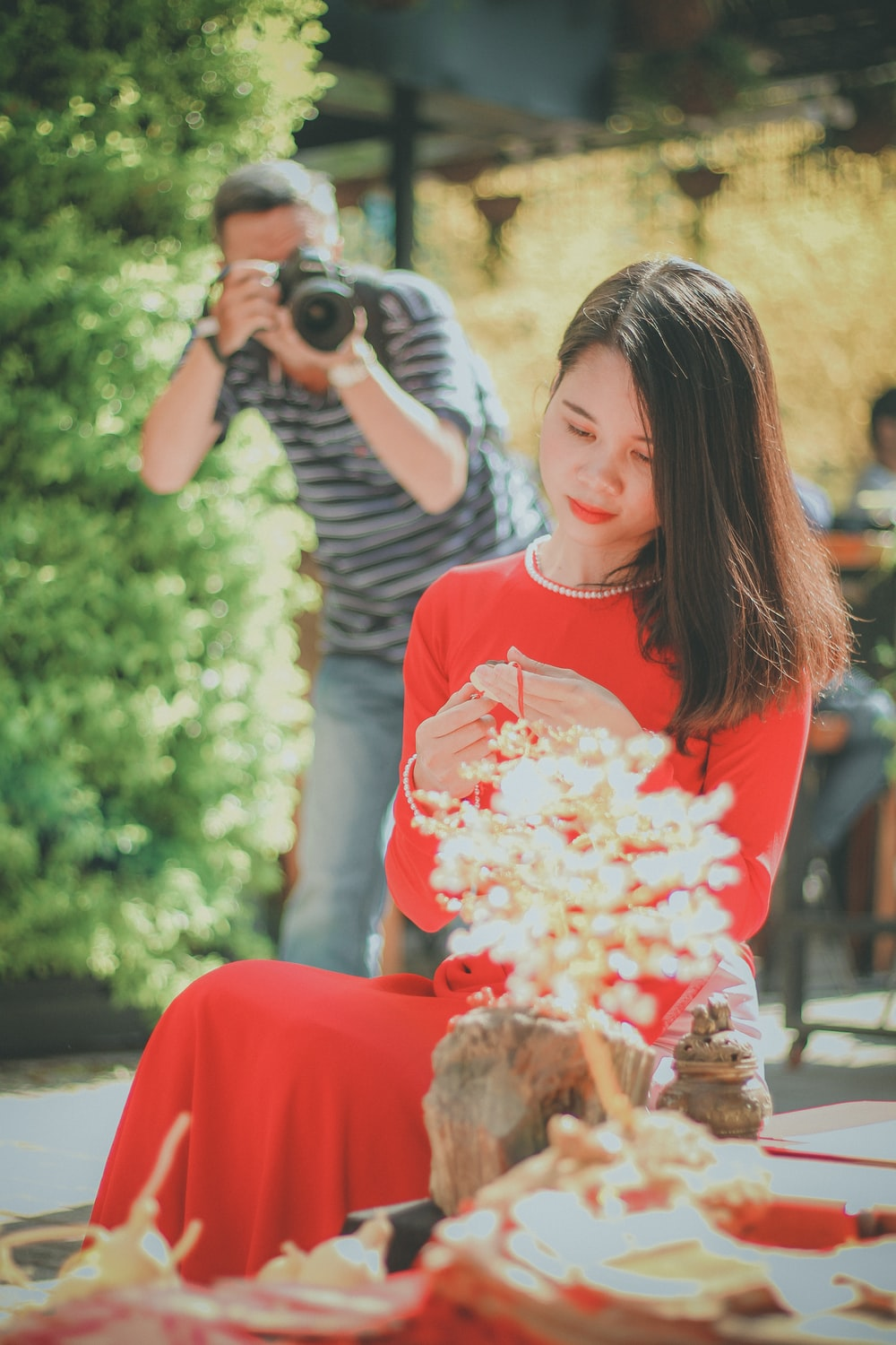 man taking photo of girl sitting in front of white flowers