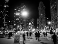 grayscale photo of people on street and buildings