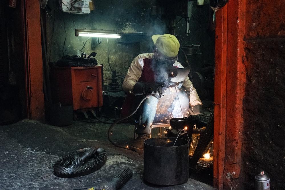 man welding an item inside room
