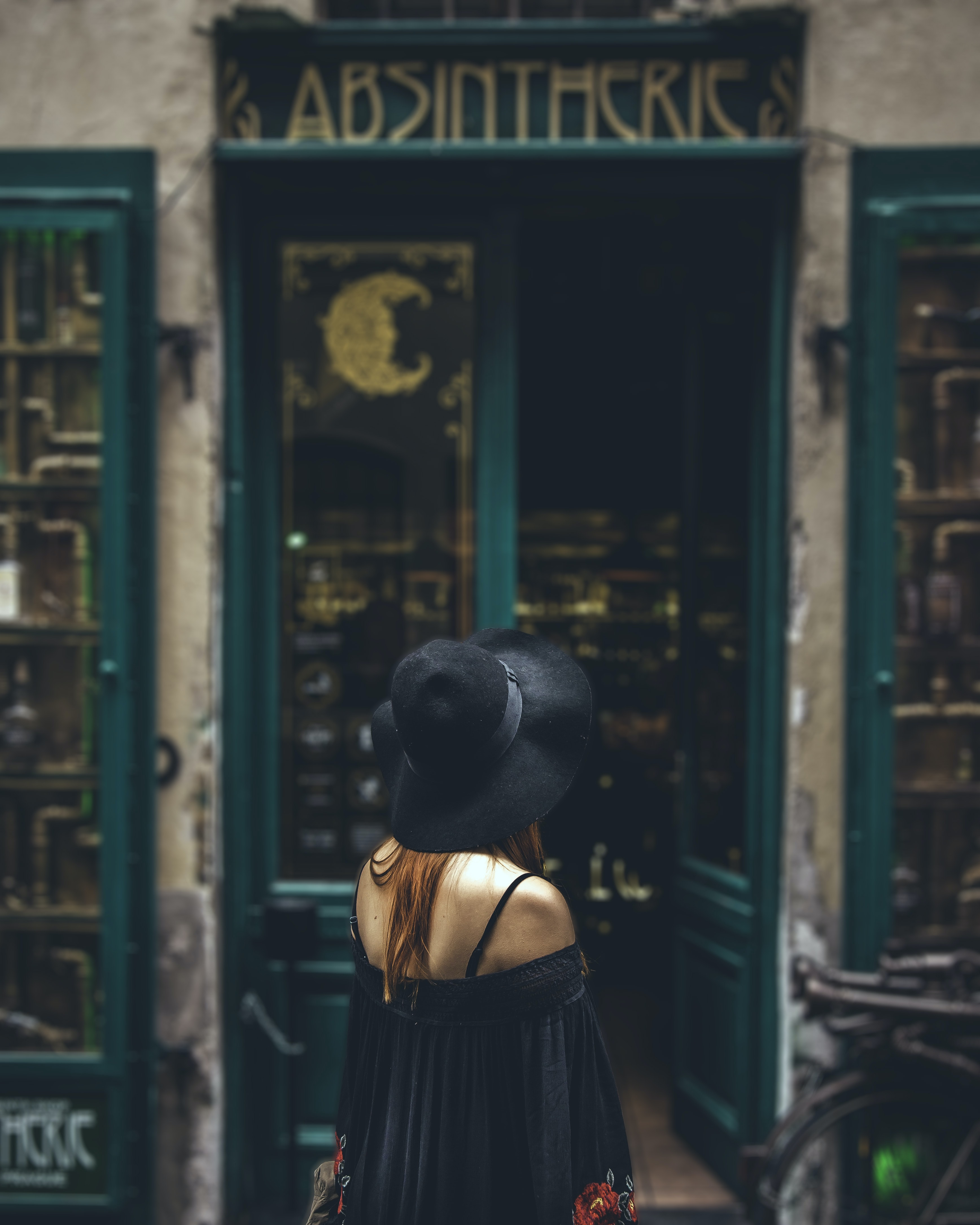 woman in black off-shoulder top and sun hat looking at green colored door building\
