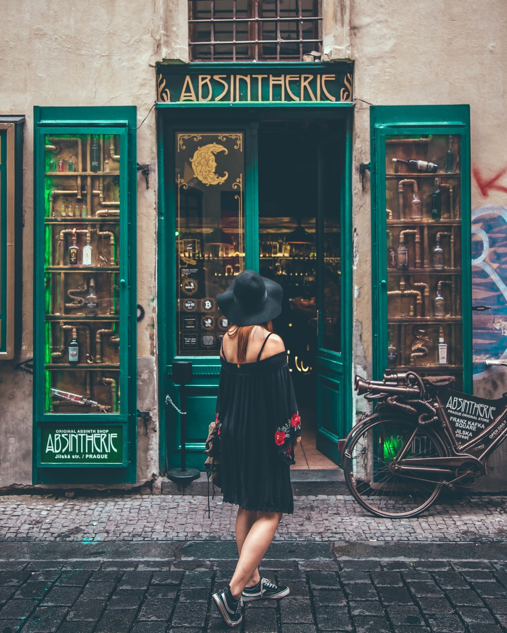 woman in black off shoulder dress and black sun hat looking at green colored door building