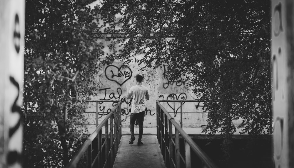 grayscale photography of man standing on bridge