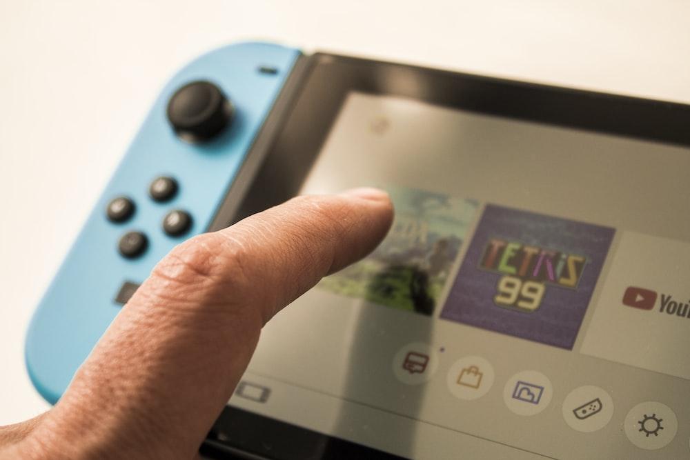 person touching Nintendo Switch