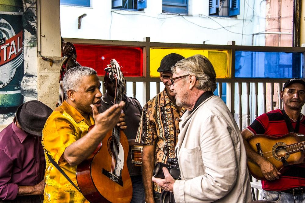man talking with man holding guitar