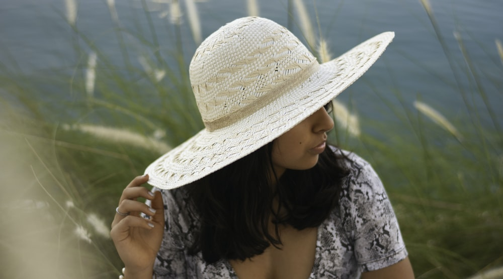 woman wearing white and black floral top holding brown straw hat