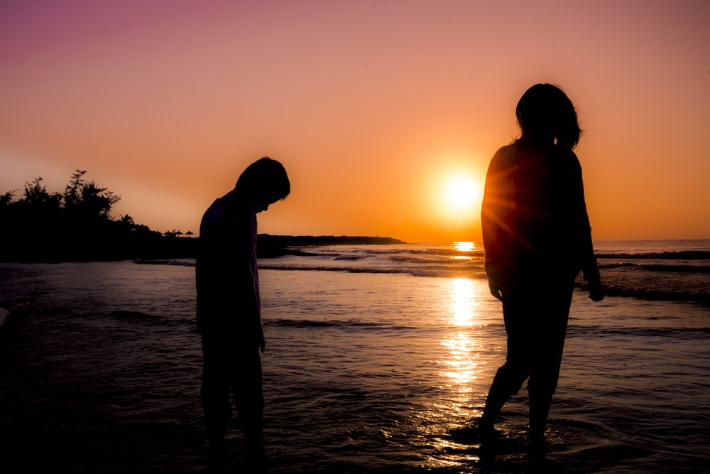 silhouette photography of boy and girl standing at beach