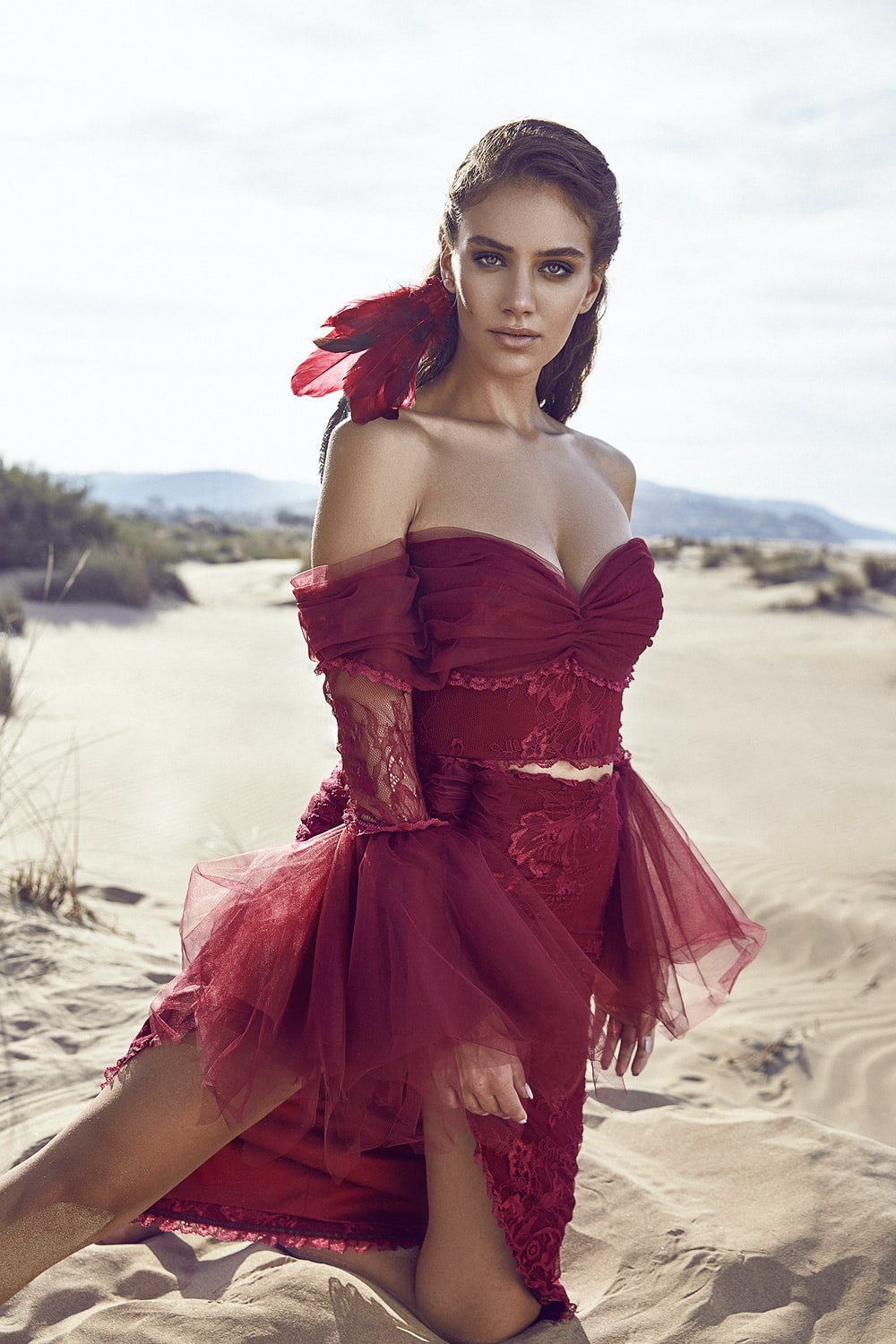 woman wearing red dress kneeling on sand