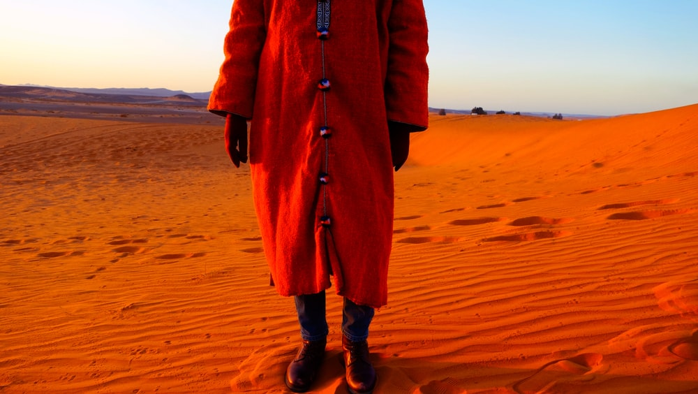 person wearing red coat standing on desert sands